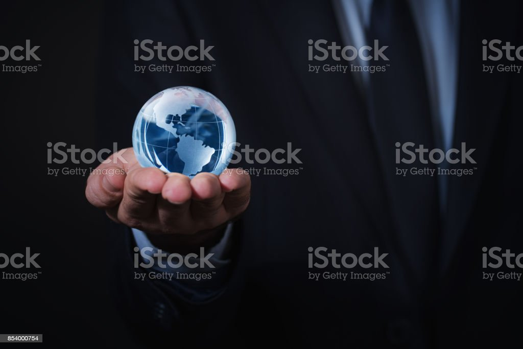 Businessman holds Earth in a hand stock photo