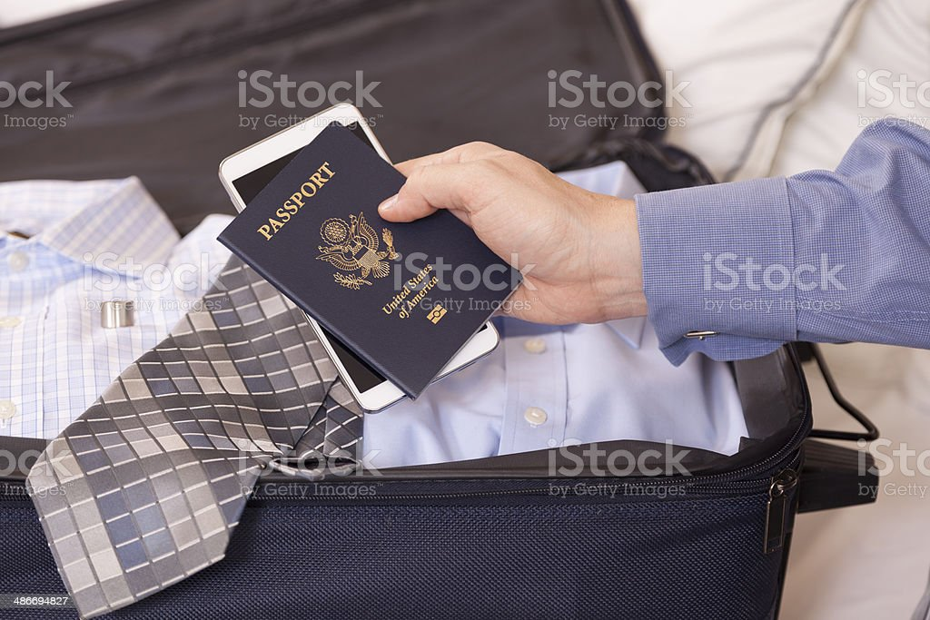 Businessman holds passport and cell phone in hotel room. Luggage. stock photo