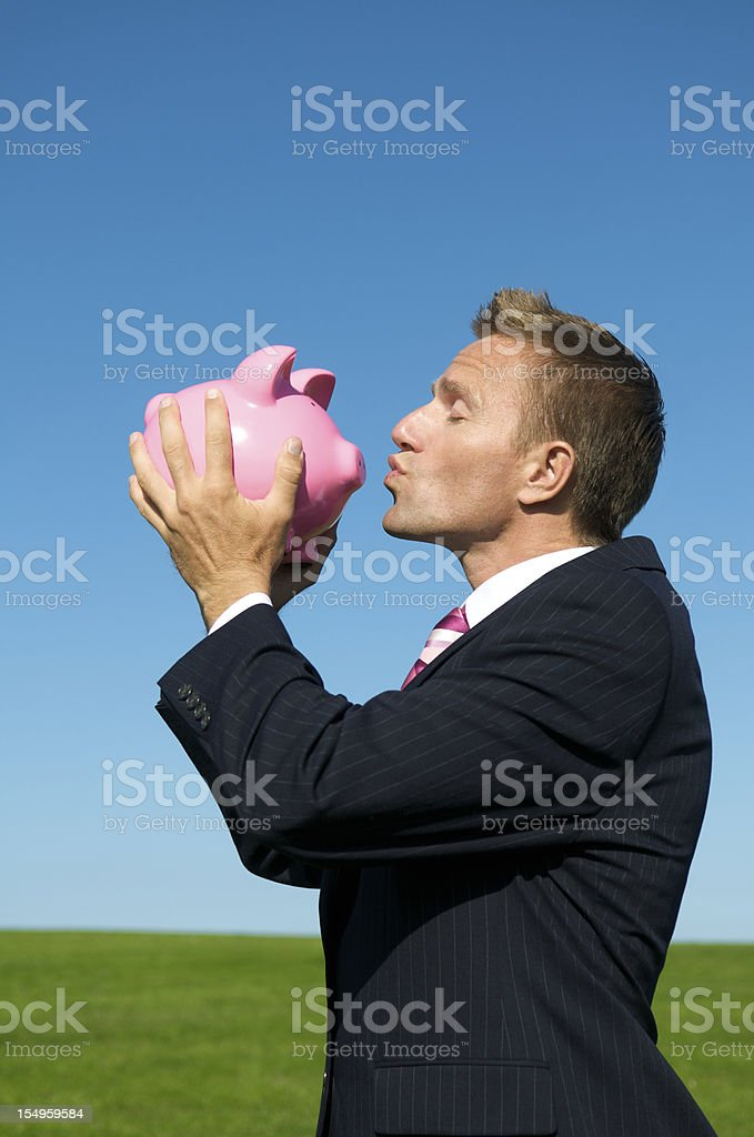 Businessman Holds Piggy Bank Up for a Kiss royalty-free stock photo