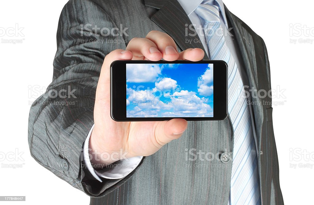 Businessman holds smart phone with cloud computing concept royalty-free stock photo