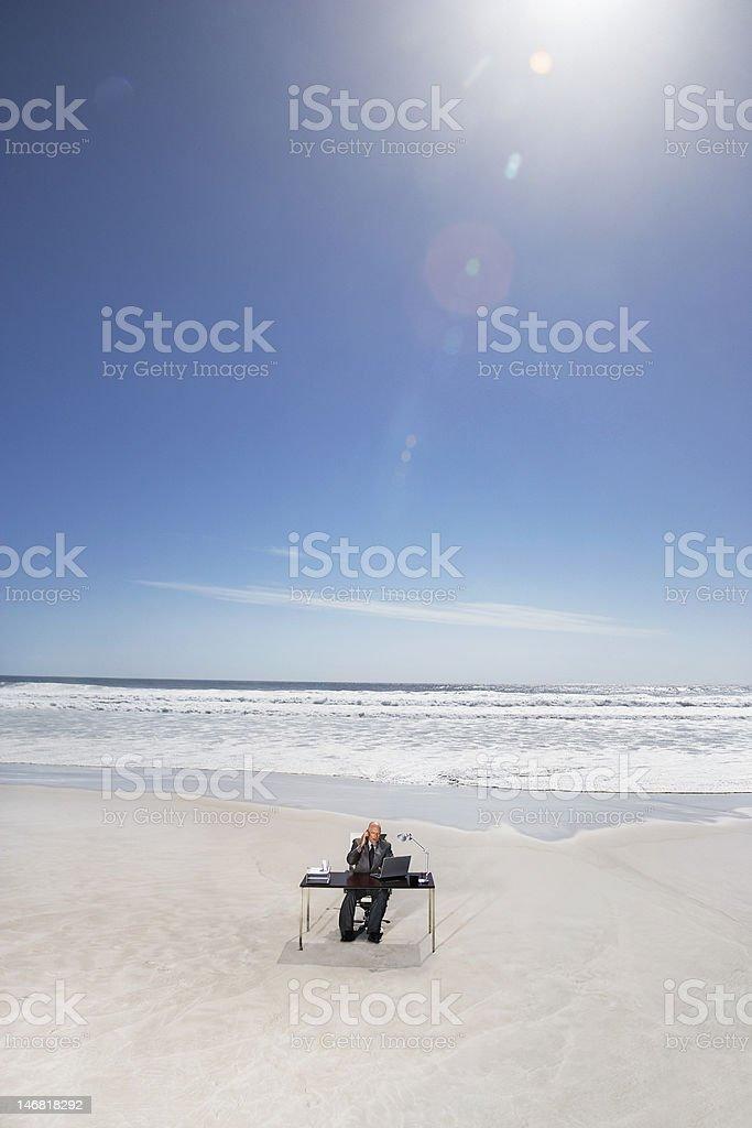 Businessman hot desking at remote beach royalty-free stock photo