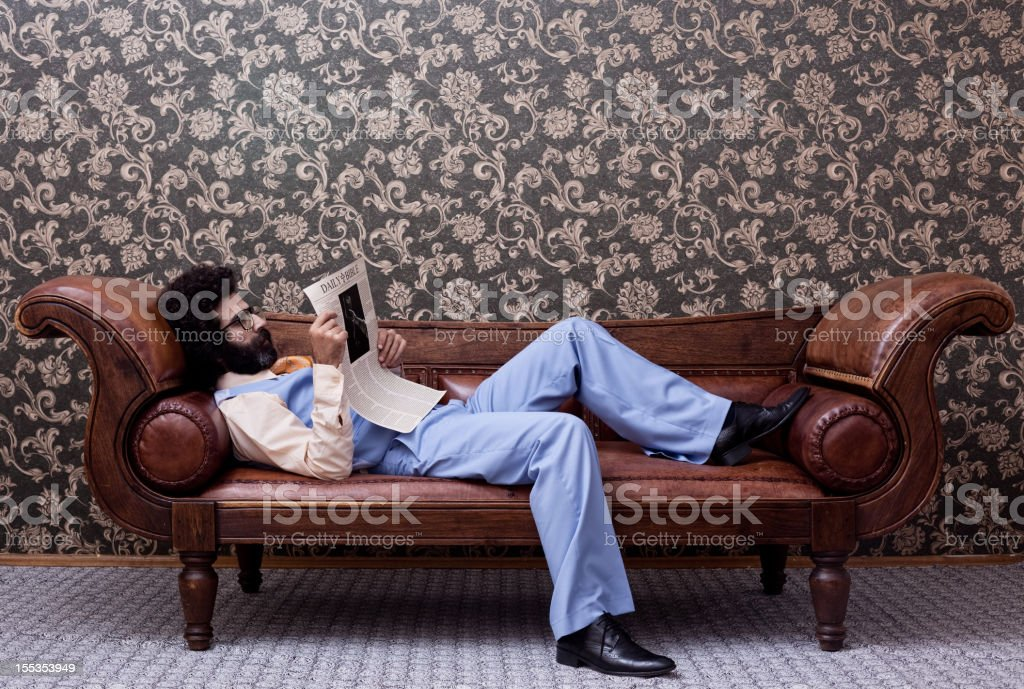 Businessman in 1970s style sitting on sofa and reading newspaper royalty-free stock photo