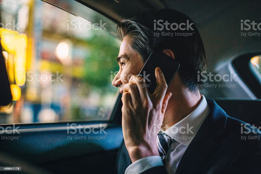 Businessman in a car at night stock photo