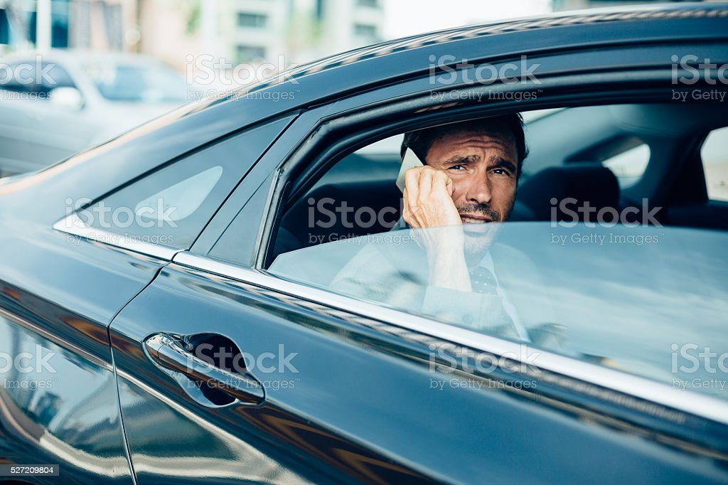 Businessman in a car talking on the phone stock photo