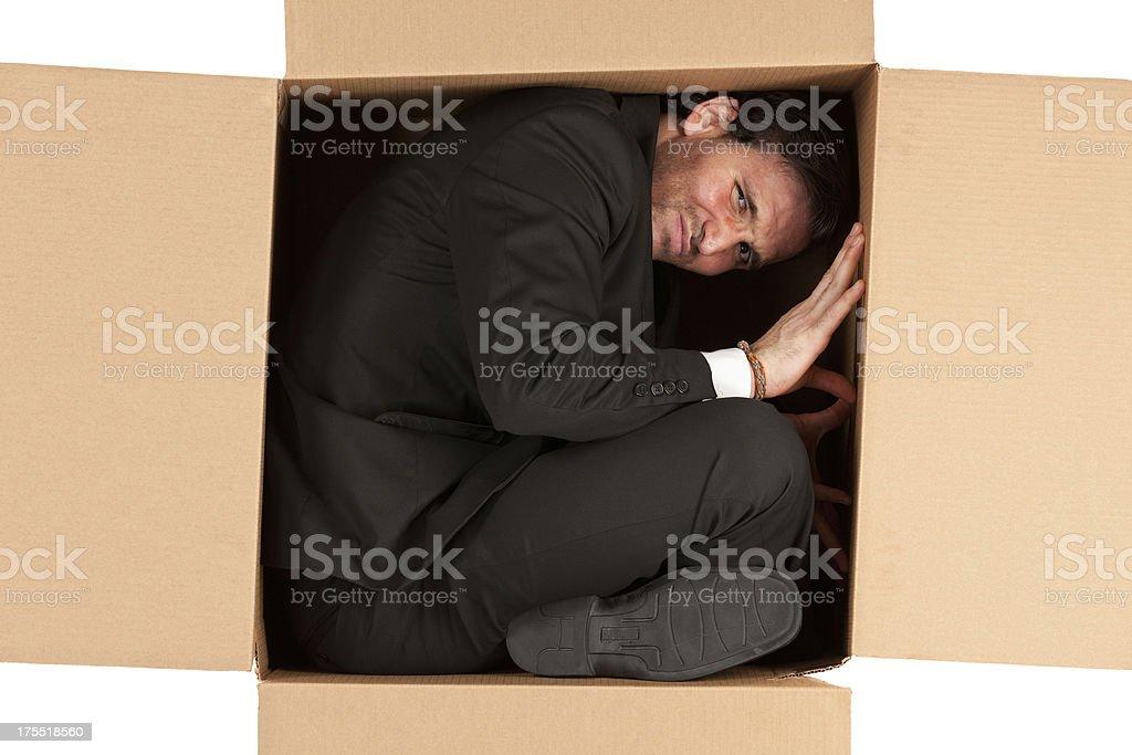 Businessman in a cardboard box stock photo