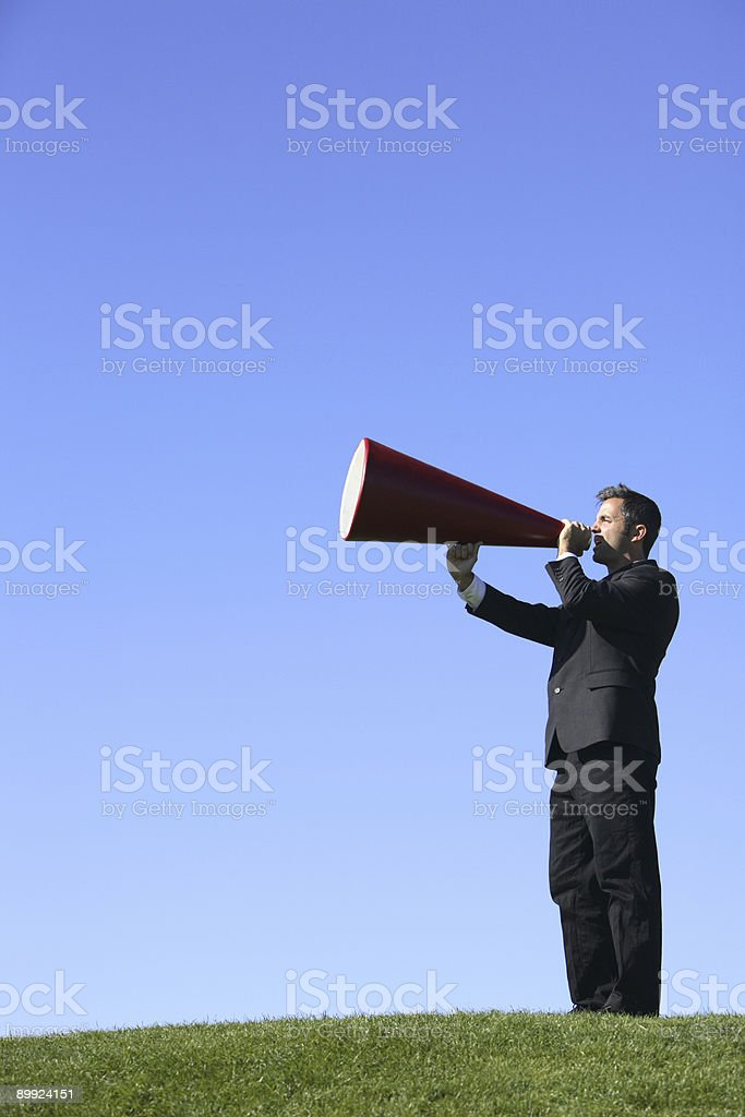 A businessman in a field with a megaphone royalty-free stock photo
