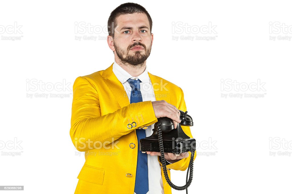 businessman in a gold suit hangs up the phone stock photo