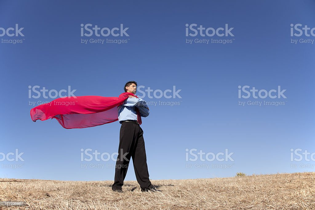 Businessman in a red cape standing in the sun stock photo
