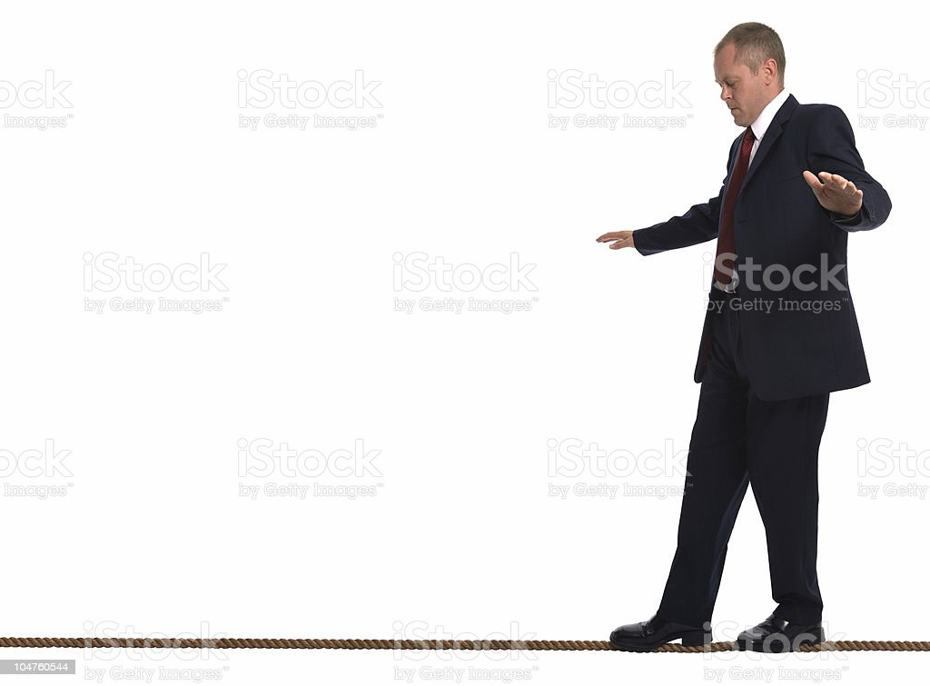 Businessman in a suit balancing on a tightrope stock photo