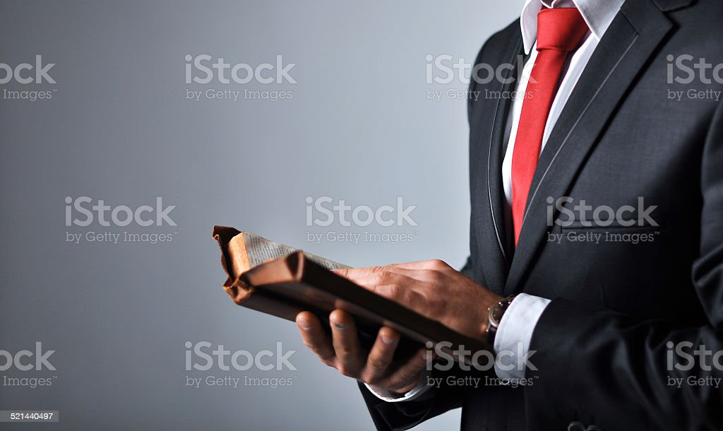 Businessman in a suit holding a book stock photo