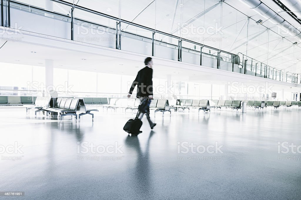 Businessman in a suit walks in airport terminal stock photo