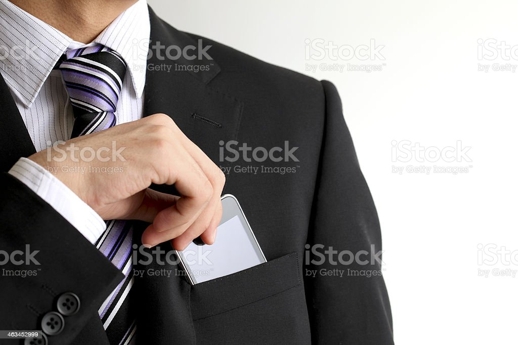 A businessman in a suit with a smartphone stock photo