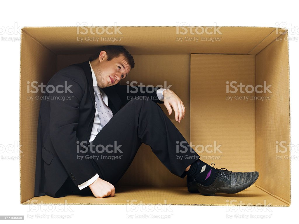 Businessman in a tight cardboard stock photo