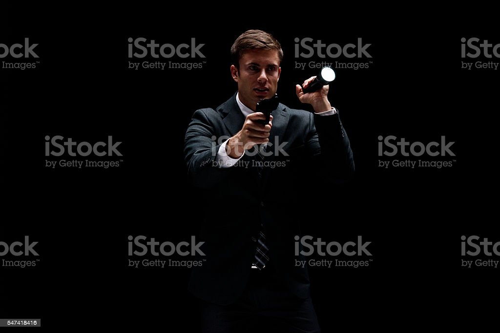 Businessman in action with gun and flash light stock photo
