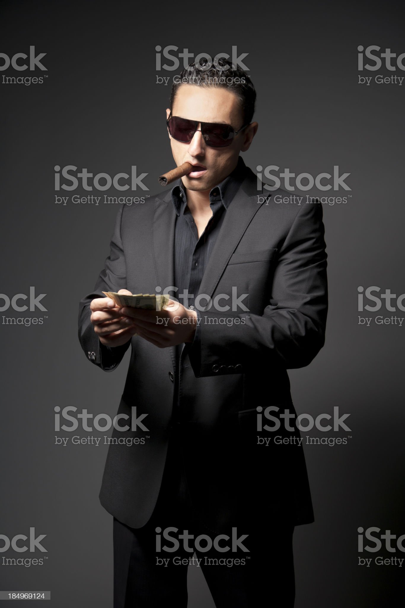 Businessman in black suit with a cigar and money royalty-free stock photo