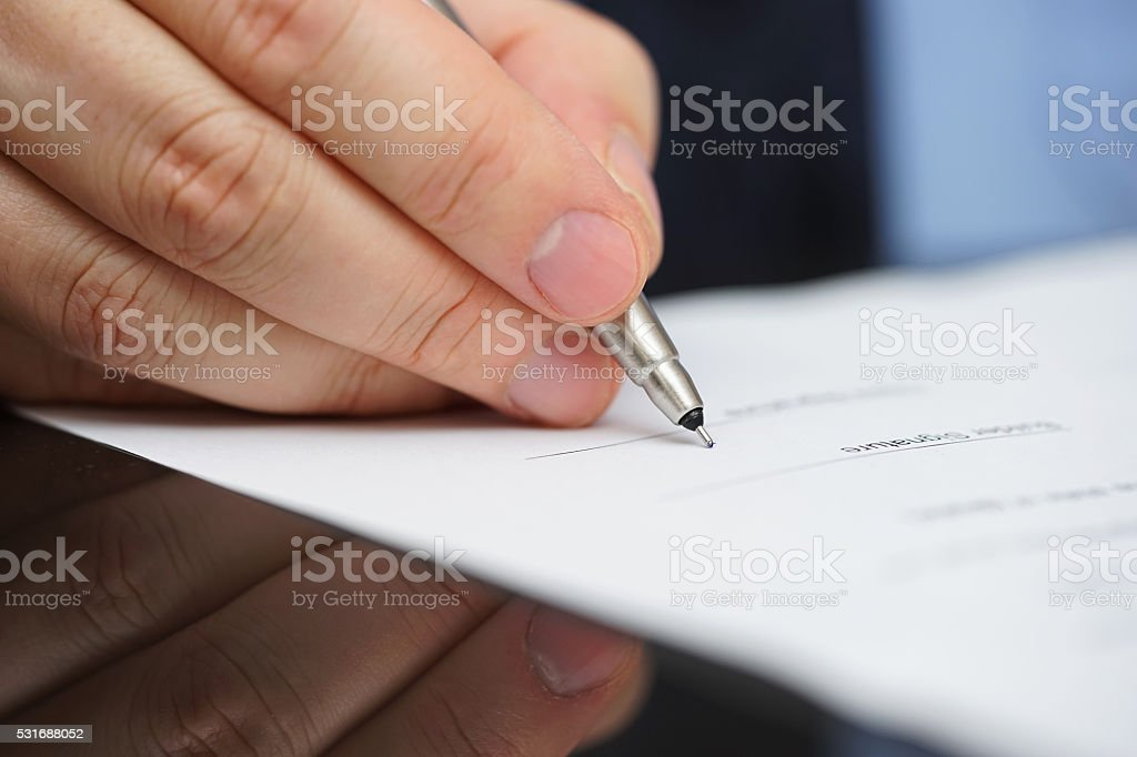 businessman in blue shirt  and tie signing contract stock photo