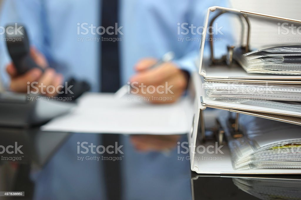 businessman in blur is working at office desk with phone stock photo