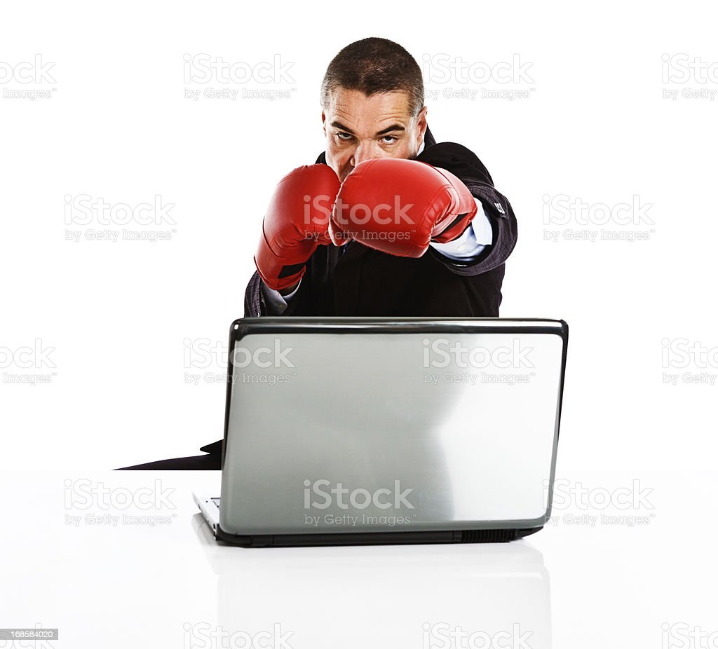 Businessman in boxing gloves defends his laptop royalty-free stock photo