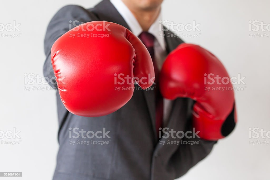 Businessman in boxing gloves launching a punch isolated stock photo