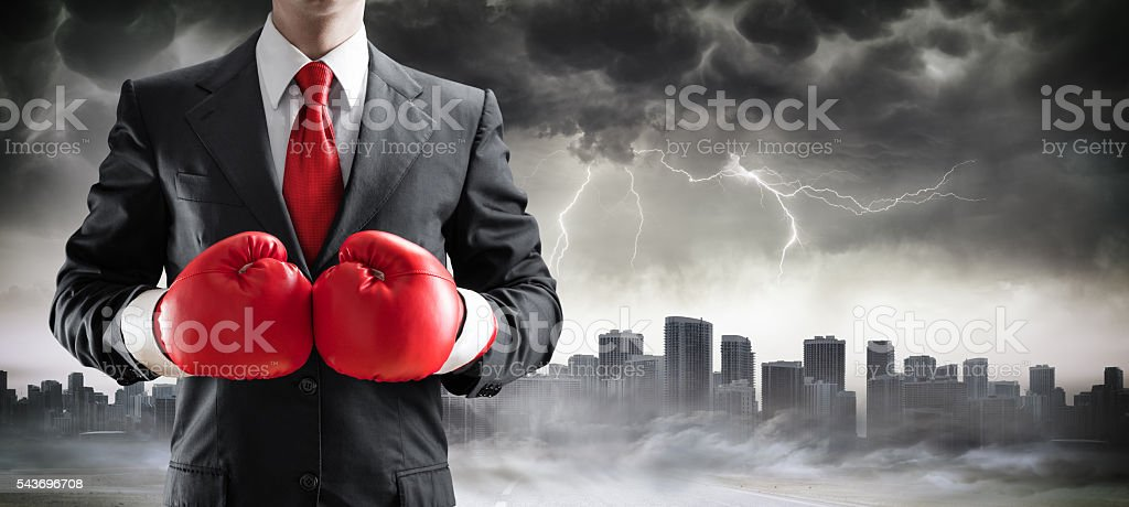 Businessman In Boxing Gloves With Cityscape In Storm stock photo