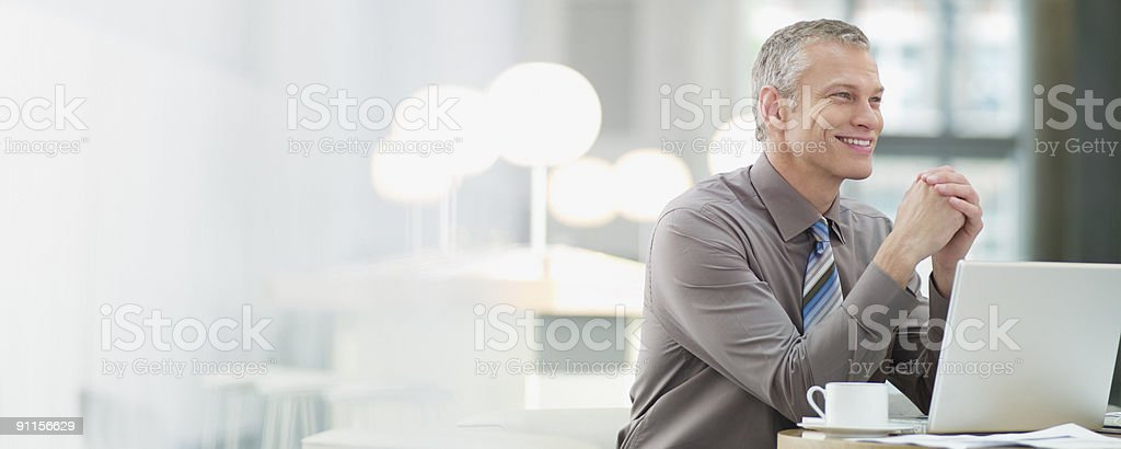 Businessman in cafeteria with laptop stock photo