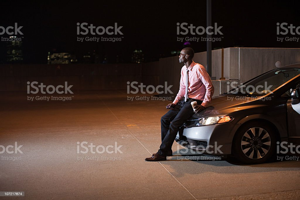 Businessman in car park at night royalty-free stock photo