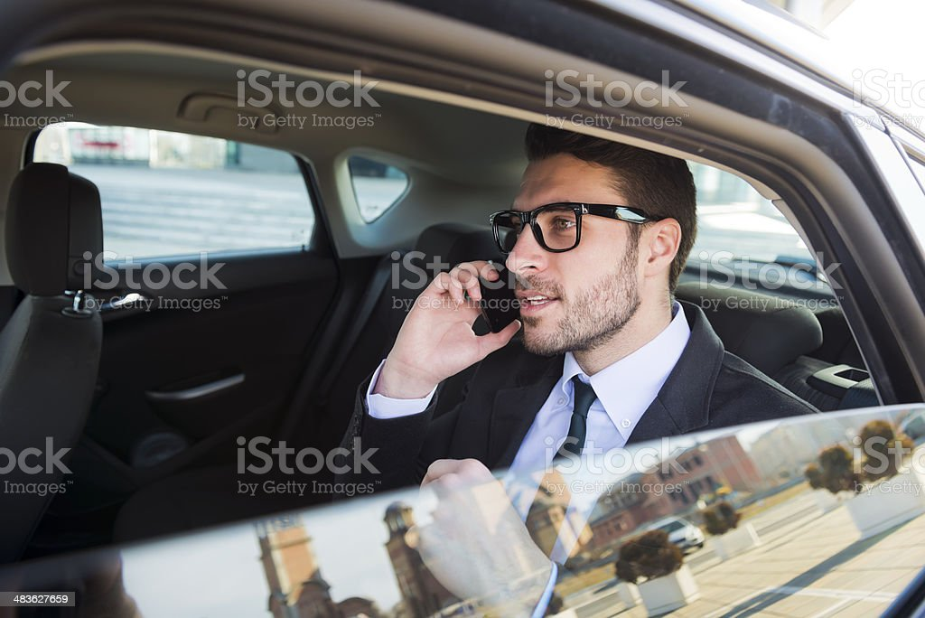 Businessman in car talking on cell phone stock photo