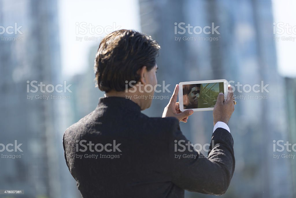 Businessman in City Taking Photo with Computer Tablet royalty-free stock photo