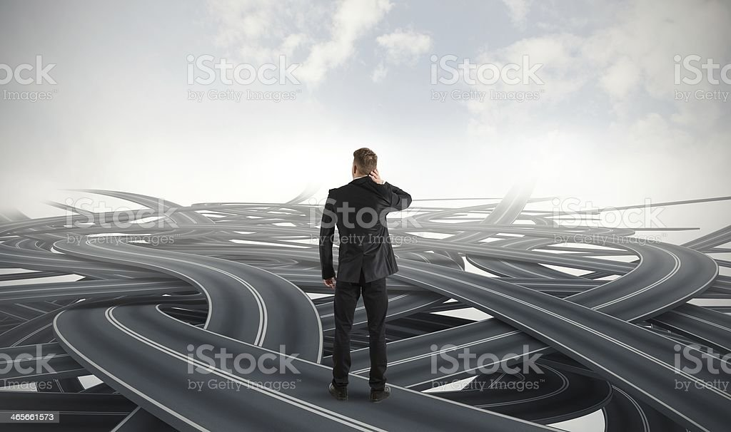 Businessman in crisis facing different roads stock photo