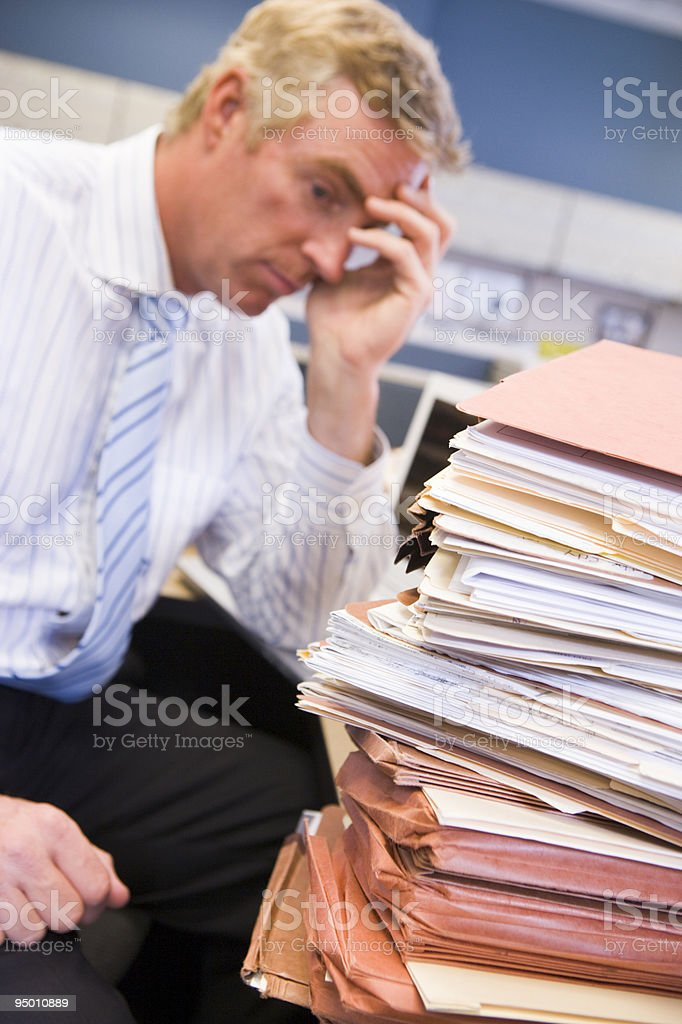 Businessman in cubicle with stacks of files stock photo