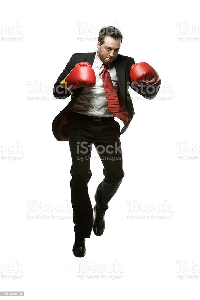 Businessman in dark suit jumping with red Boxing gloves. stock photo