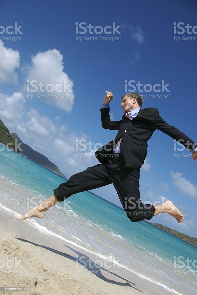 Businessman in Dark Suit Leaps on Beach royalty-free stock photo