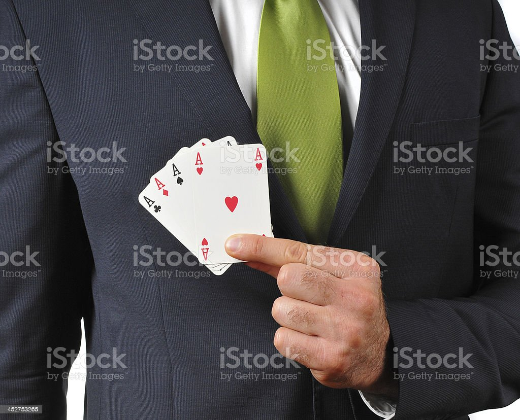 Businessman in dark suit with necktie showing poker of aces stock photo