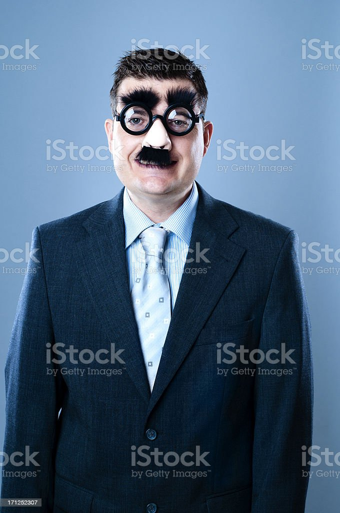 Businessman in disguise tries to smile stock photo