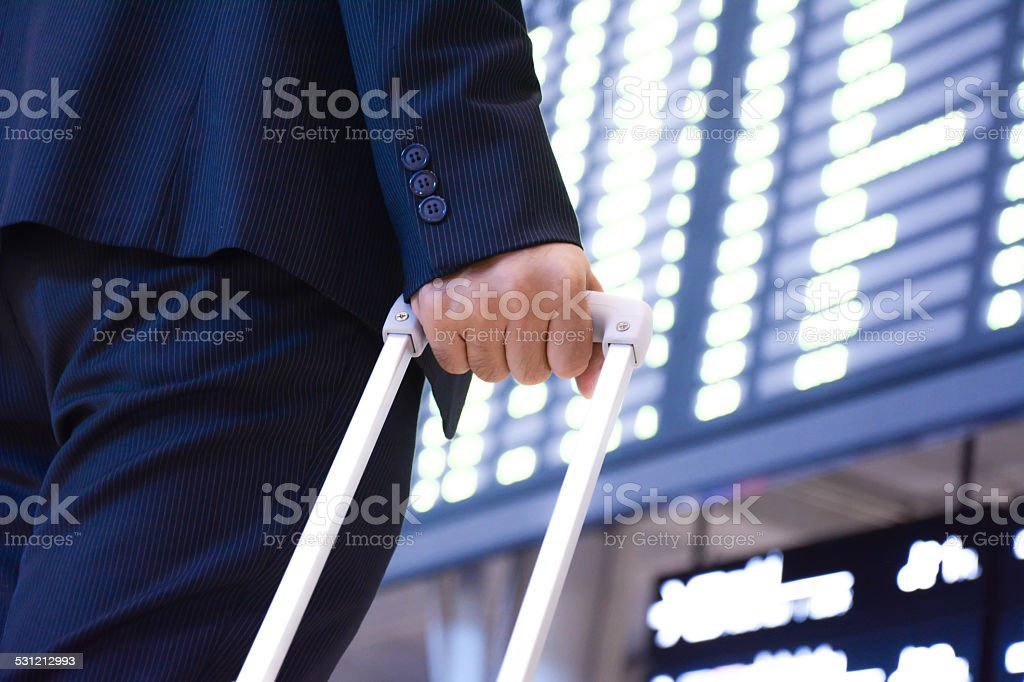 Businessman in front of airport timetable holding trolley bag stock photo