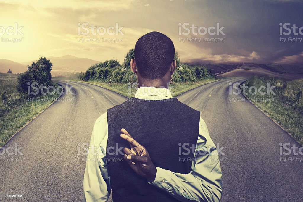 businessman in front of two roads fingers crossed stock photo