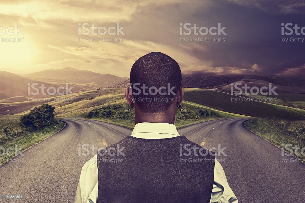 businessman in front of two roads stock photo