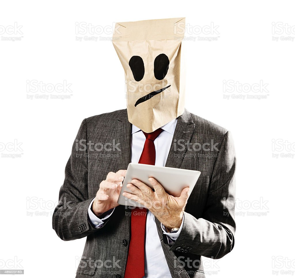 Businessman in frowning paper-bag mask holding digital tablet stock photo