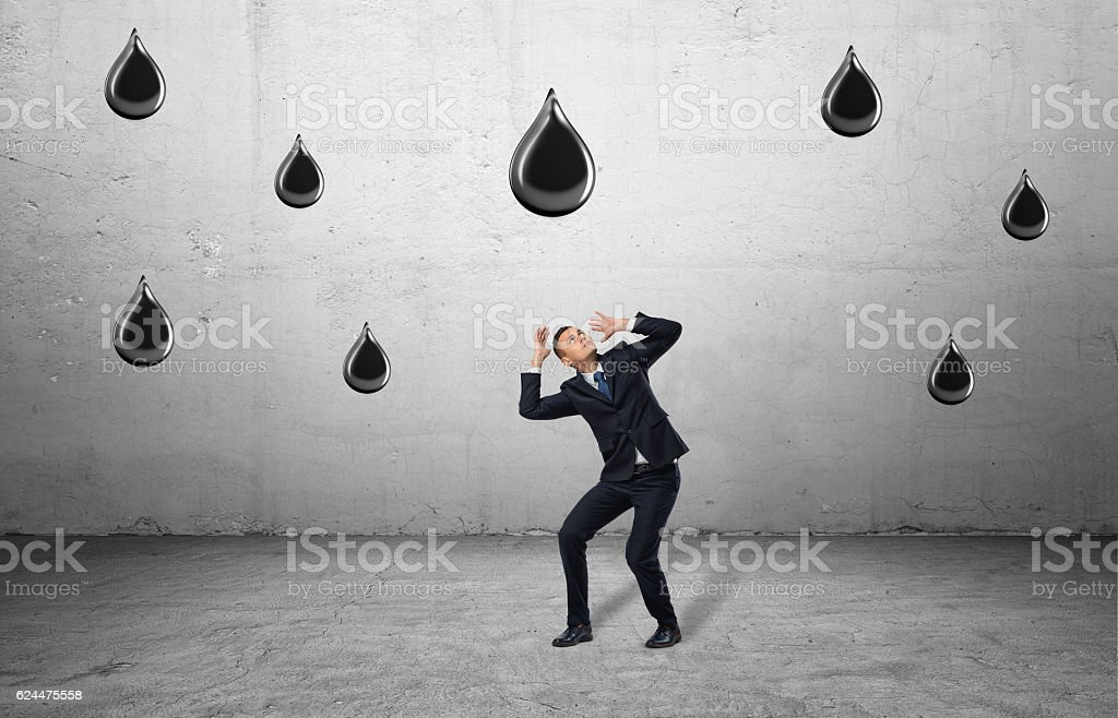 Businessman in full growth protects himself against huge falling oil vector art illustration