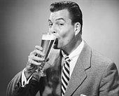 Businessman in full suit drinking beer in studio, (B&W), portrait