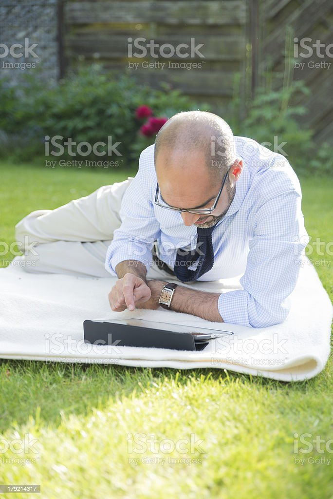 Businessman in garden with tablet pc royalty-free stock photo