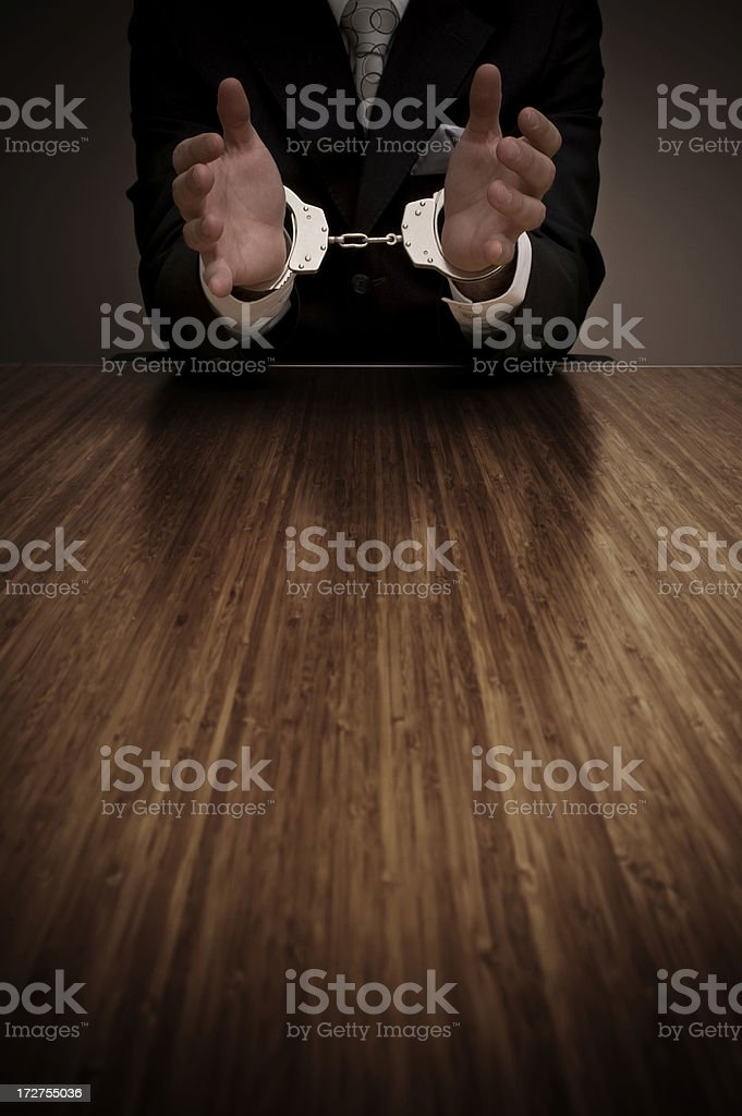 Businessman in handcuffs sitting at table royalty-free stock photo