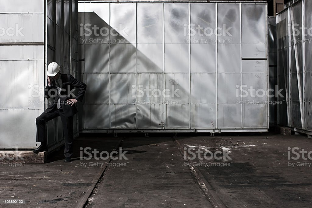 Businessman in hard hat by container stock photo