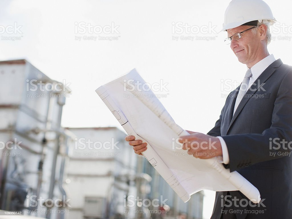Businessman in hard-hat reviewing blueprints outdoors royalty-free stock photo