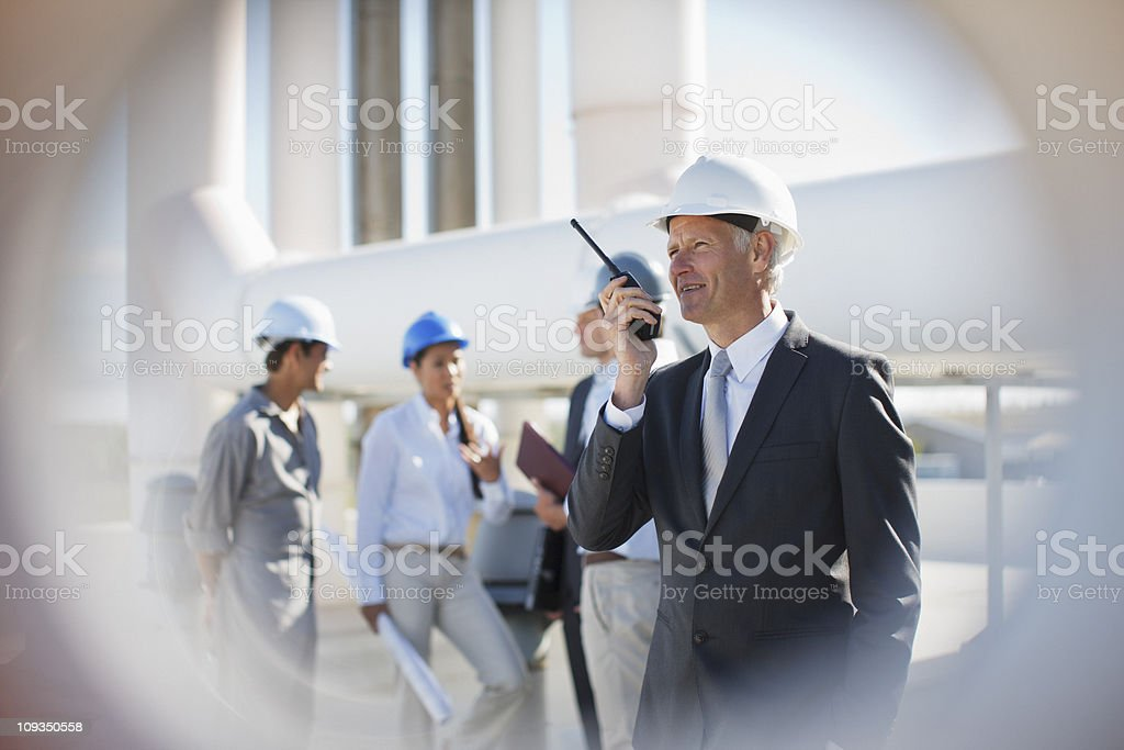 Businessman in hard-hat talking on walkie-talkie outdoors royalty-free stock photo