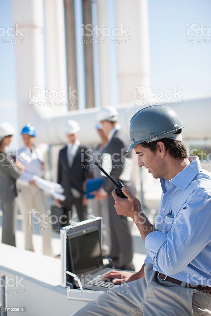 Businessman in hard-hat talking on walkie-talkie outdoors stock photo