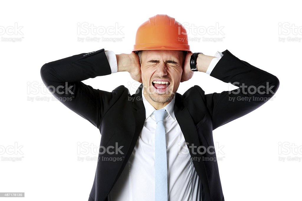 Businessman in helmet covering his ears stock photo
