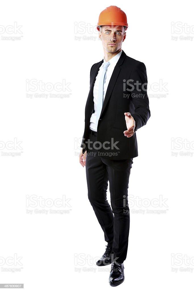 businessman in helmet offering handshake stock photo