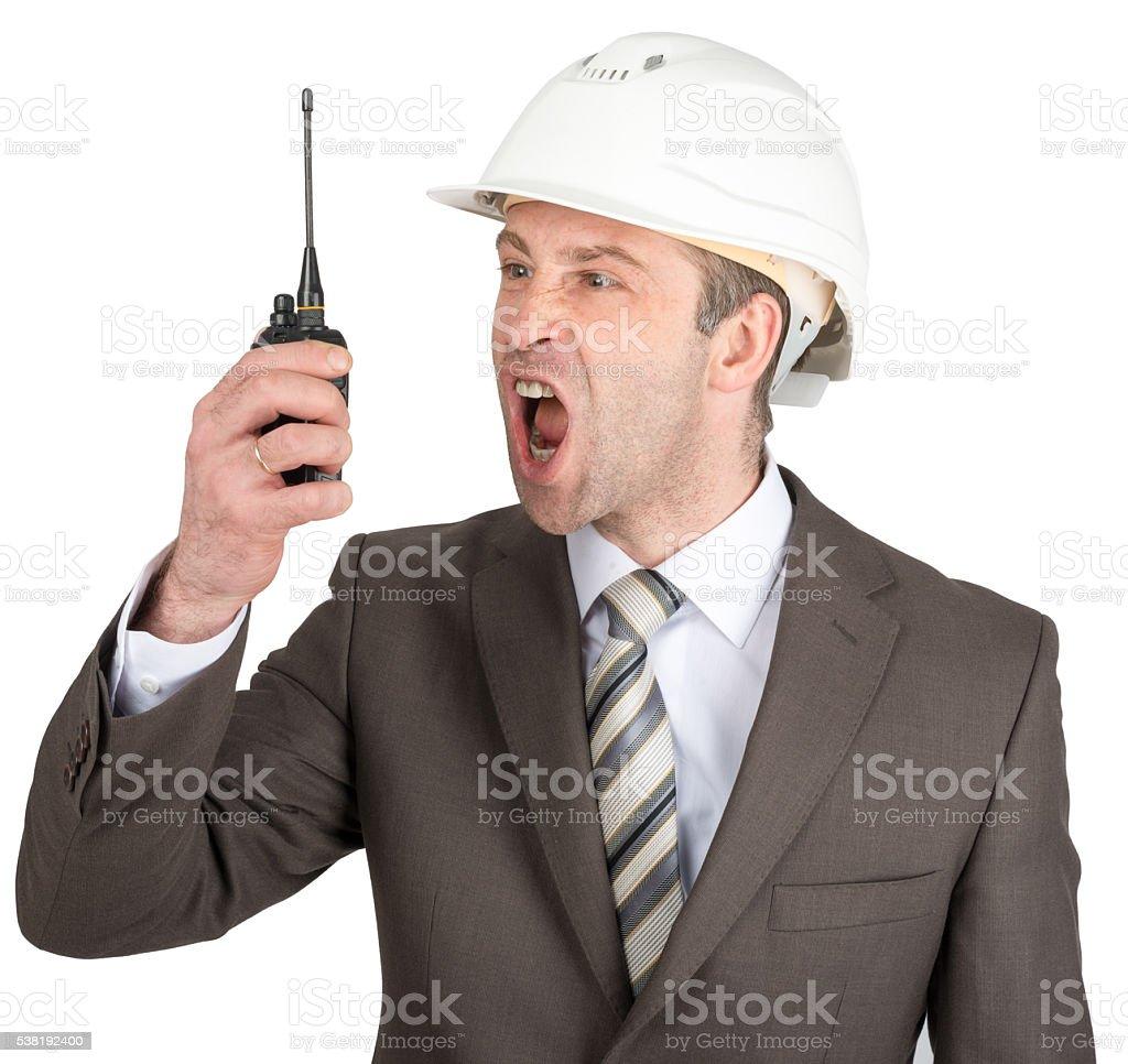 Businessman in helmet screaming at walkie-talkie stock photo
