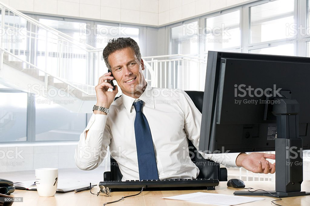 Businessman in his office on the phone at his desk royalty-free stock photo